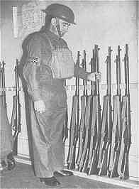 An Image Showing A Home Guard Member Checking his Unit's Rifles